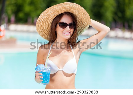 Charming young woman enjoying a cocktail upon a swimming pool - stock photo
