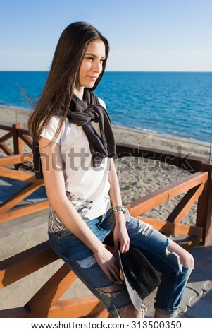 Charming young woman enjoying a good weather and recreation time while sitting against the sea in sunny afternoon, stylish female hipster rest after strolling along the beach in spring season