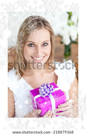 Charming young woman holding a present sitting on the floor against snowflakes - stock photo