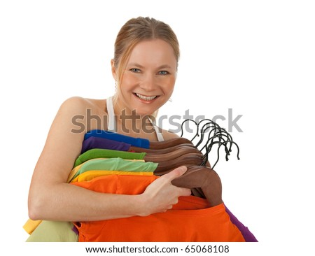 Charming young woman holding lots of colourful clothes on hangers. Isolated on white. - stock photo