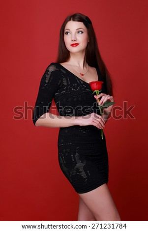 Charming young woman in a black dress holding a single red rose on a red background - stock photo