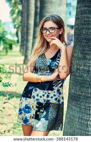 Charming young woman in a light summer dress with glasses. She looks into the camera and smiles. Outdoor.