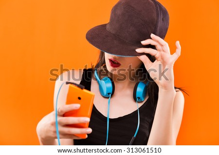 Charming young woman, in black blouse and cap, holding smart phone in her hand and blue headphones hanging on her neck - isolated on orange background, in studio, waist up - stock photo