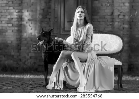 Charming young woman in long beautiful dress sitting on sofa outdoor with dog breed mastiff on natural background black and white, horizontal picture - stock photo