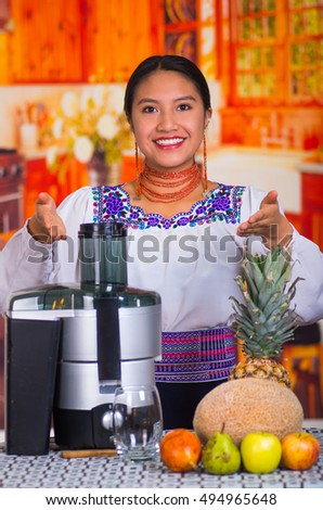Charming young woman in traditional andean dress standing inside kitchen posing in front of juice maker, healthy lifestyle concept