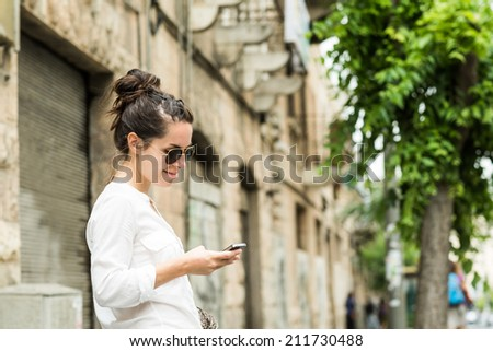 Charming young woman in white shirt reads or texts message to mobile phone, against old grunge houses in old city.  - stock photo