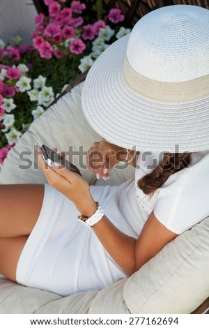 Charming young woman in white summer dress sitting down outside sending text message on cellphone. - stock photo