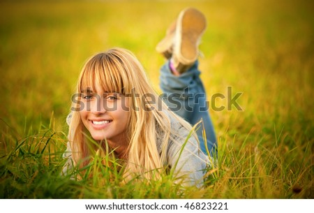 Charming young woman lies on summer lawn and smiles. - stock photo
