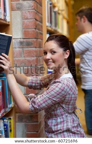 Charming young woman looking for a book in a bookstore - stock photo