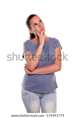 Charming young woman looking left up on blue shirt against white background - copyspace - stock photo