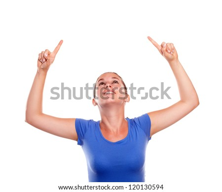 Charming young woman pointing and looking up standing over white background - copyspace - stock photo