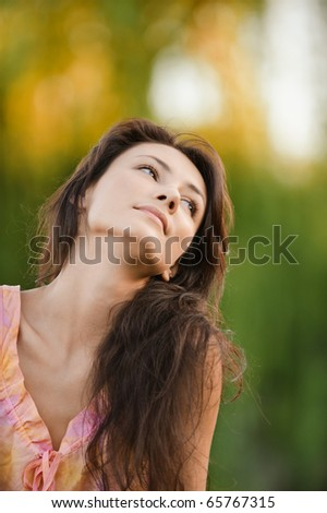 Charming young woman recollects former life, against city park. - stock photo