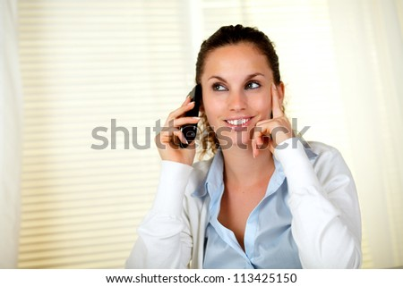 Charming young woman smiling while listening on cellphone at office - copyspace - stock photo