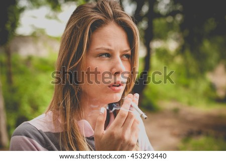 charming young woman smoking a cigarette nature outdoors, family problems, domestic violence, a way to keep the mind. vintage colors - stock photo