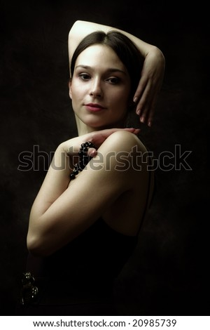 charming young woman, studio dark - stock photo