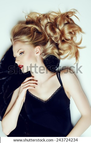 Charming young woman with beautiful blonde hair lying on furs. Luxury, rich lifestyle. Fashion photo. - stock photo