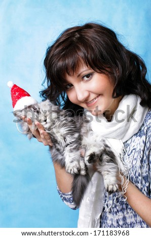 Charming young woman with cat isolated on blue background - stock photo