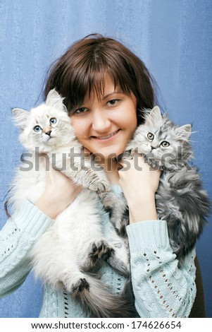 Charming young woman with kittens on blue background - stock photo