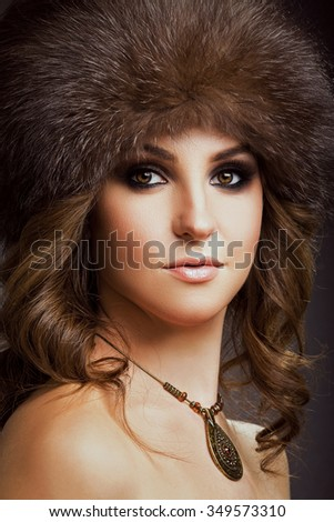 Charming young woman, with necklace on her neck, wearing in brown fur hat, posing on gray background, in studio, waist up