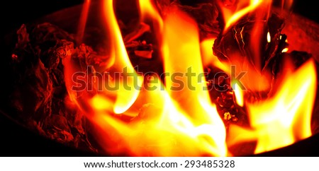 charred paper in a container, burning bright flame - stock photo