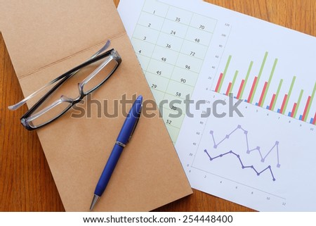 chart and note book on the wooden table - stock photo