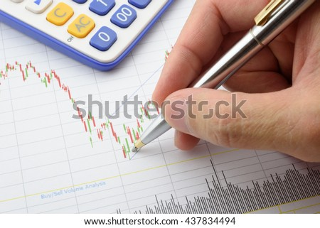 Chart / graph / indicator of financial instruments for technical trend analysis has been analysed by businessman / equity analyst with a blue ballpoint pen pointing on red / green candle stick signal. - stock photo