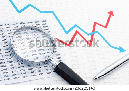 Chart, graph, magnifying glass and pen on the line graph. Making graph. Analyzing data with magnifying glass.  - stock photo