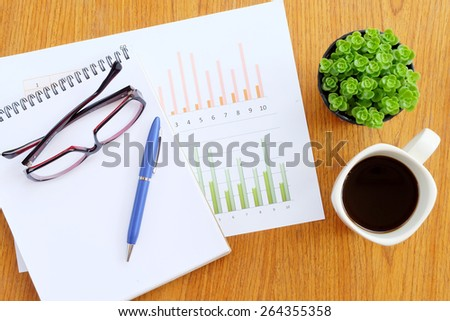 chart on the wooden table with hot coffee - stock photo