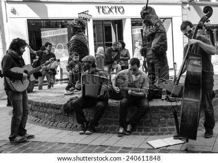 CHARTRES, FRANCE - APRIL 14, 2013: Four undefined street musicians and the public. Hundreds of buskers perform on the streets in France.