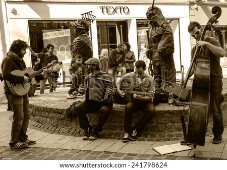 CHARTRES, FRANCE - APRIL 14, 2013: Four undefined street musicians and the public. Hundreds of buskers perform on the streets in France. - stock photo