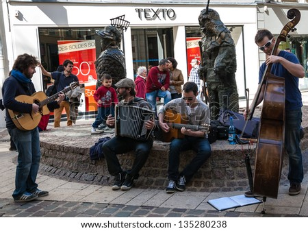 CHARTRES, FRANCE - APRIL 14: Four unidentified street musicians and the public as seen on April 14, 2013 in Chartres, France Hundreds of buskers perform on the streets in France. - stock photo