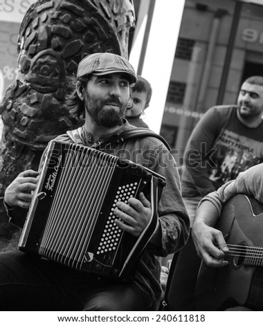 CHARTRES, FRANCE - APRIL 14, 2013: Undefined street musician and the public. Hundreds of buskers perform on the streets in France. - stock photo