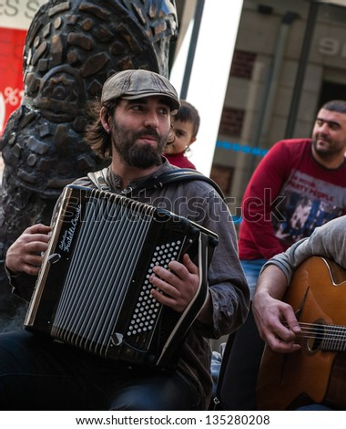 CHARTRES, FRANCE - APRIL 14: Unidentified street musician and the public as seen on April 14, 2013 in Chartres, France. Hundreds of buskers perform on the streets in France. - stock photo