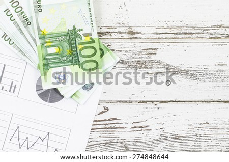 Charts and money on wooden table - stock photo