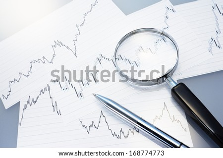 Charts, magnifier and pen. Analyzing exchange fluctuation.