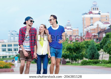 Chat friends. Young friends have fun together on the street and smile at each other. - stock photo