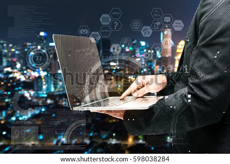 Chatbot and internet of things concept. Double exposure of Electric circuit graphic , technology chat bot icons. Business man suit hand holding to laptop computer with blur bokeh city background.
