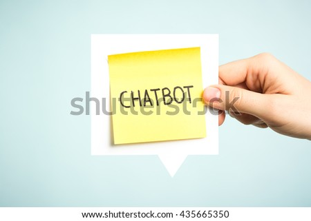 Chatbot concept. Hand holding a speech bubble with yellow note with the word chatbot. - stock photo