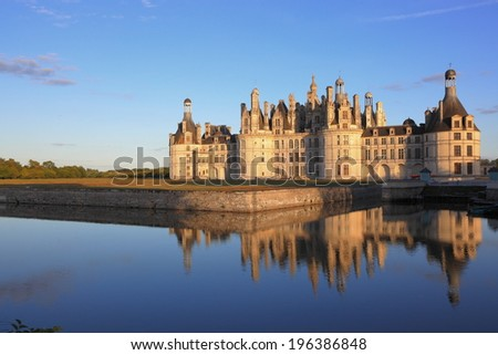 Chateau Chambord with reflection at sunset - stock photo
