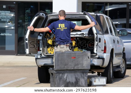 CHATTANOOGA, TN/USA - JULY 18: An FBI agent gathers evidence at the Armed Forces Career Center in Chattanooga, TN on July 18, 2015. An attack on the center was carried out on July 16th, 2015.