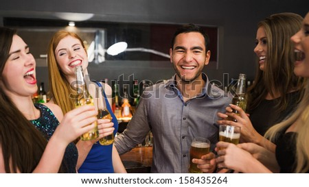 Chatting friends drinking beer and laughing in the nightclub - stock photo