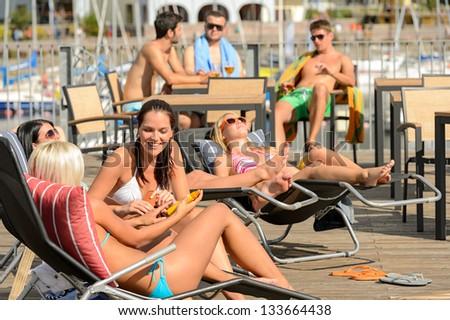 Chatting girls lying on deckchair sunbathing in bikinis sunny day - stock photo