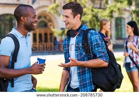 Chatting with friends. Two young men talking to each other and smiling while two women standing in the background - stock photo