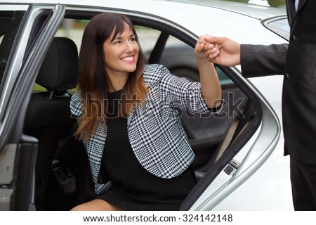 Chauffeur helping young business woman to get out from a luxury car - stock photo