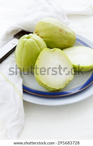 Chayotes on a plate, one of them sliced on a white background  - stock photo