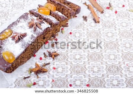 Chcolate spices cake with star anise and dried fruits, cinnamon, cloves, cardamom, handmade milk chocolate with nuts on sackcloth, canvas. Sweet frame. Free space for your text. - stock photo