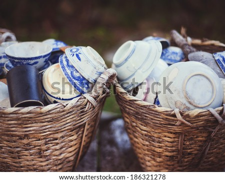 Cheap ceramic cups, plates and bowls in basket on a street market for sale in Vietnam - stock photo