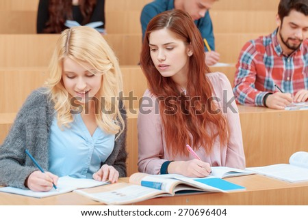 Cheating on test. Young beautiful red haired student peeping to the exercise book of her friend sitting by her side at class - stock photo