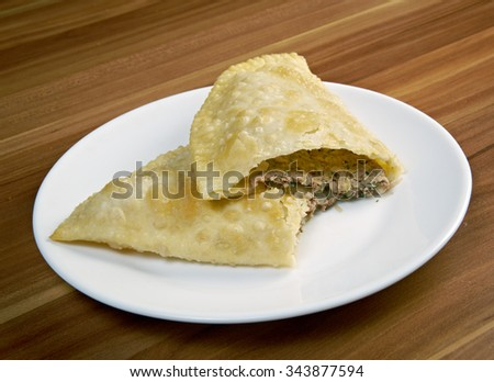 Cheburek with meat - traditional Caucasian dish.national dish of the Crimean Tatars and  Caucasian and Turkic peoples,  popular  Transcaucasia, Central Asia, Russia, Ukraine,  in Turkey and Romania. - stock photo