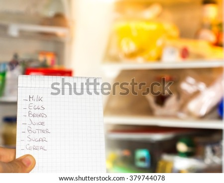Check a shopping list near the fridge - stock photo